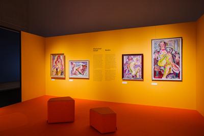 Yrjö Saarisen värikkäitä alastonmaalauksia oranssilla seinällä. Näkymä Hyvinkään taidemuseon Värinäkyjä-näyttelystä.