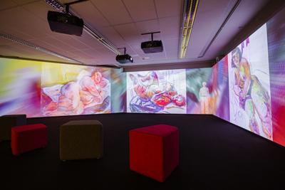 Näkymä digitaalisesta installaatiosta. Esillä kolme Saarisen kookasta alastonmaalausta ja väriliukumia.